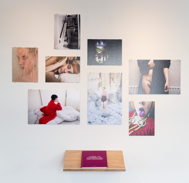 Photobook by Rikard Osterlund with some of the images from the book displayed on the wall.